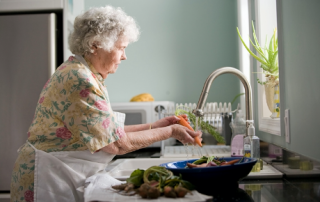 Senior washing vegetables over a sink