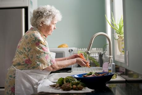 Senior washing vegetables over a sink